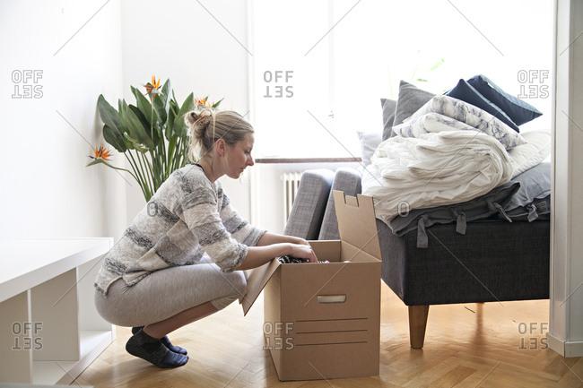 Woman putting belongings in cardboard box