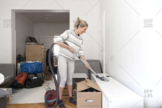 Woman vacuuming off shelves on moving day