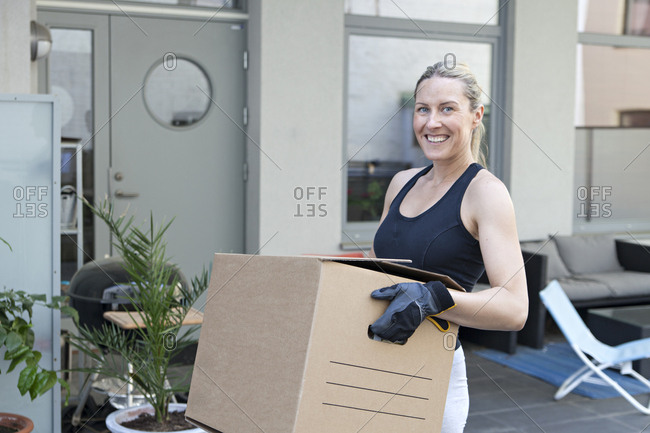 Woman carrying a cardboard box on moving day