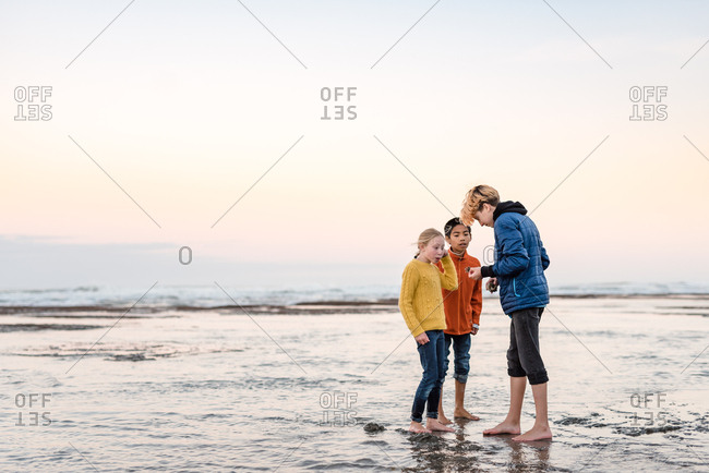 Teenage kid showing younger children shells from beach