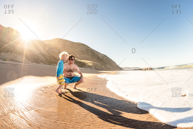 Toddler son and father on beach as tide comes in