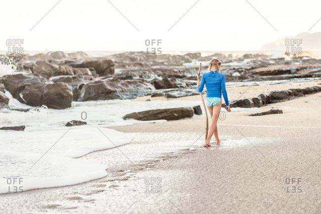 Girl exploring beach with stick