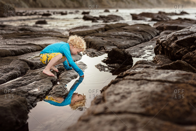 Toddler boy reflected in rock pool at beach