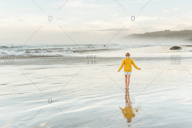 Girl in yellow sweater walking on beach
