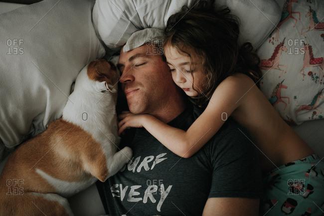 Girl lying with dad and dog