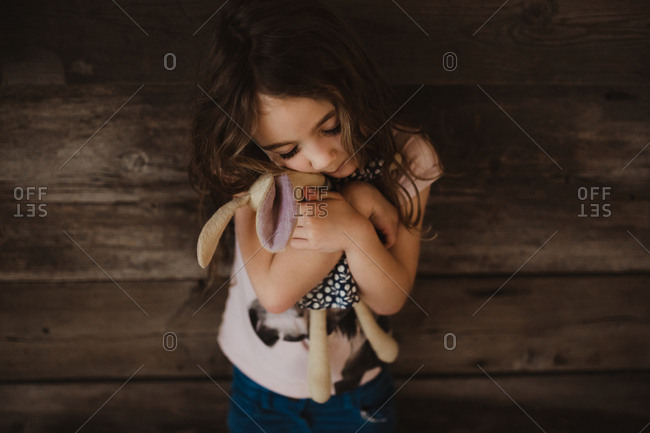 Girl hugging her doll tight