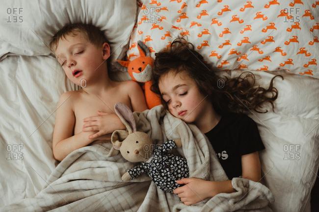 Girl and boy sleeping with dolls