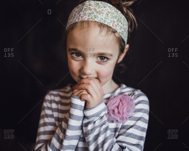 Girl in headband with shy expression
