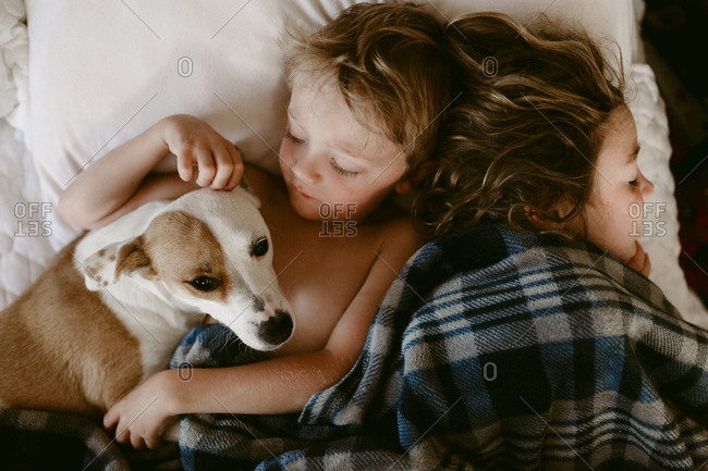 Two kids and dog snuggled in bed