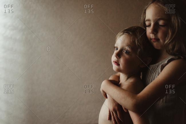 Siblings hugging together near sunlight