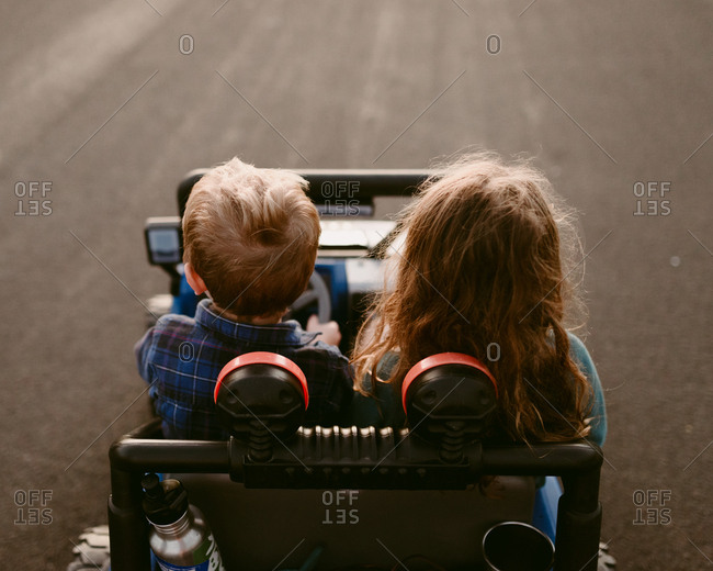 Kids in toy car together from behind