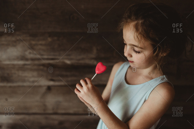 Girl holding a heart shaped lollipop