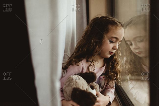 Girl hugging her doll by window