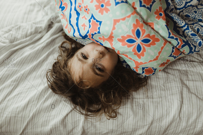 Girl smiling shyly under blanket