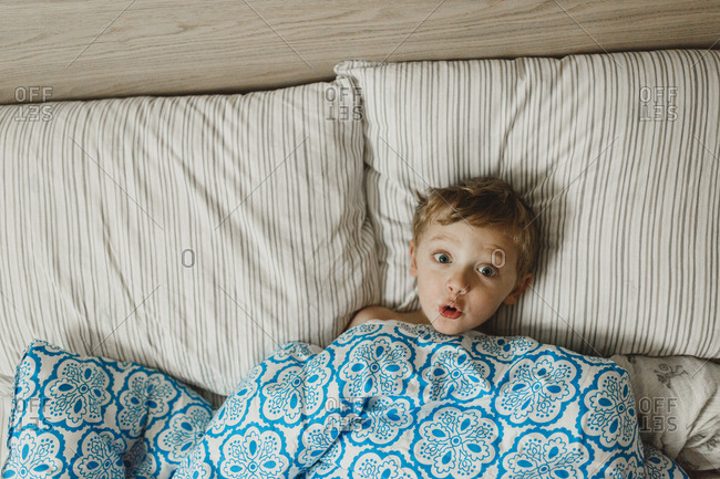 Boy making funny face under comforter