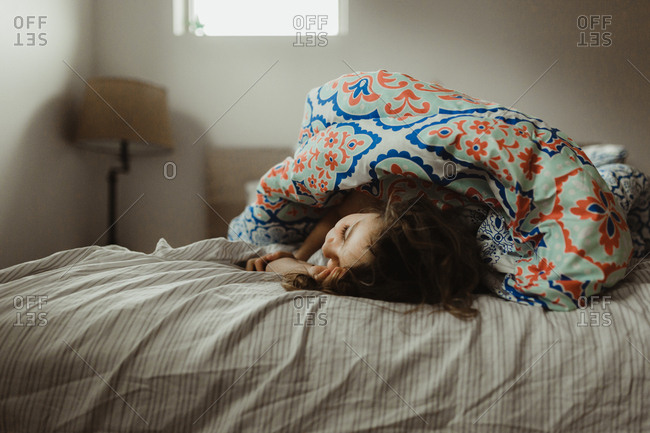 Girl wrapped in comforter on bed