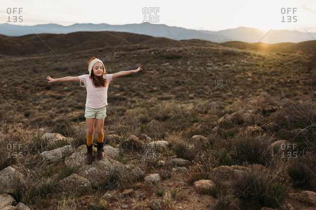 Girl with arms raised in desert hills