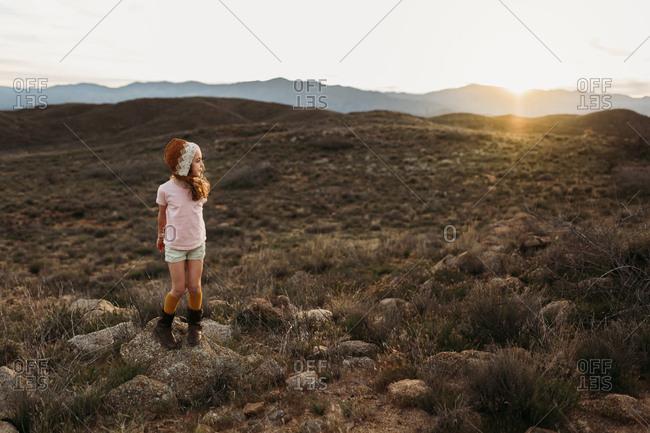 Girl standing in a desert hill setting