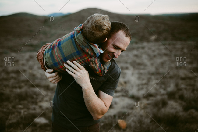 Dad and boy being playful in prairie setting