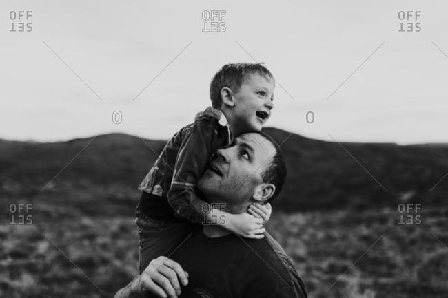 Boy on dad's shoulder in desert prairie