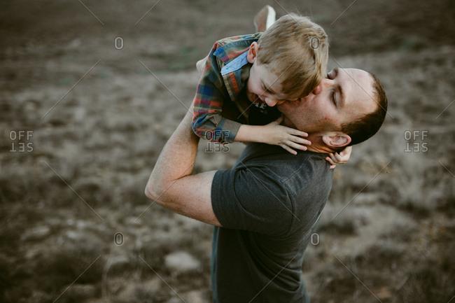 Dad kissing boy in prairie setting
