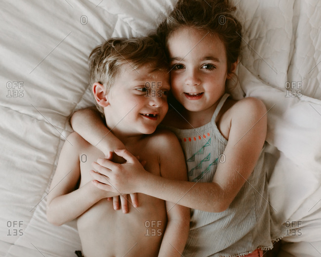 Girl snuggling with brother in bed