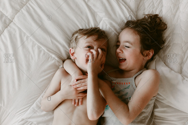 Girl and boy sharing laugh in bed
