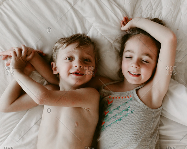 Girl and boy lounging together in bed