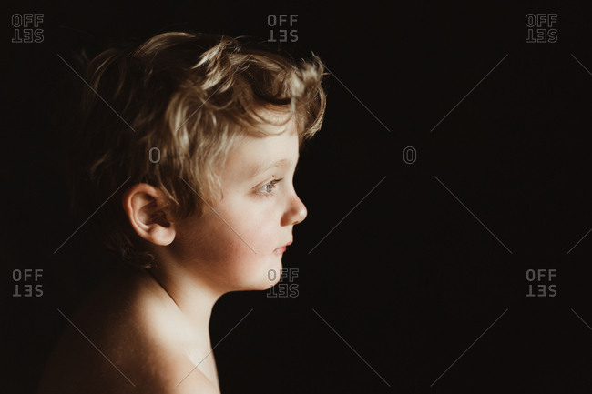 Boy in profile against black background