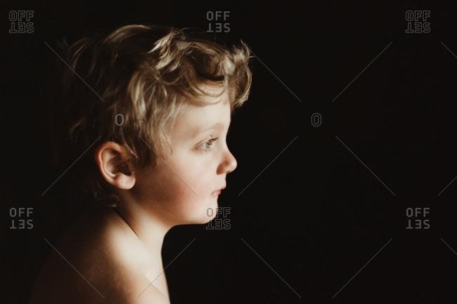 Boy in profile against black background