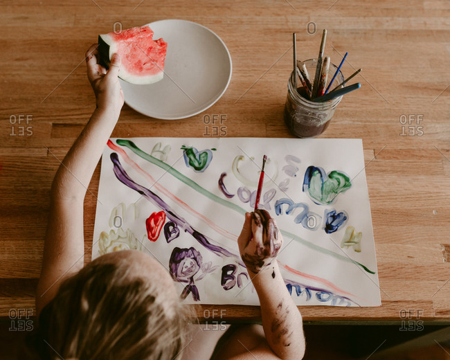 Girl painting and eating watermelon