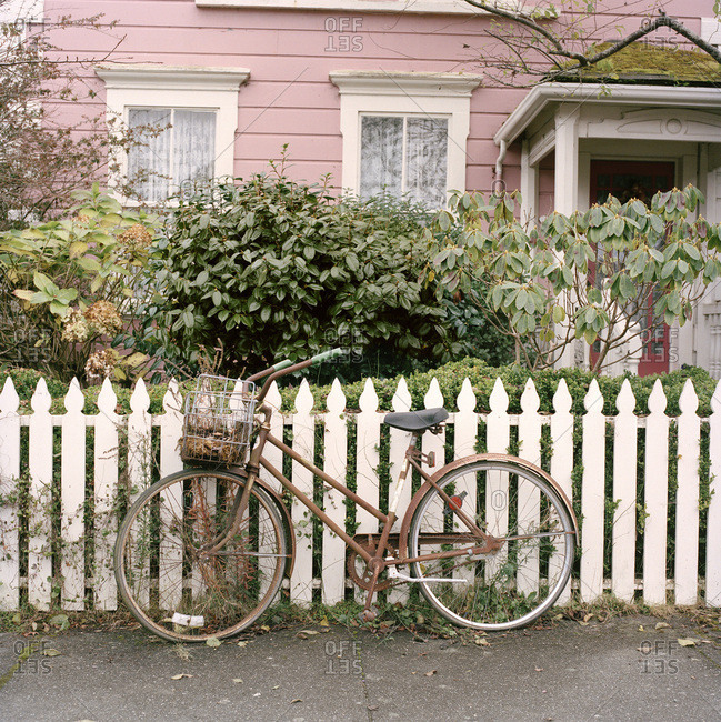 Bike with basket by white picket fence