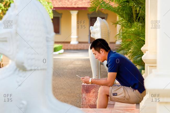 Phnom Penh, Cambodia - December 10, 2016: Tourist with a phone - Royal Palace, Phnom Penh