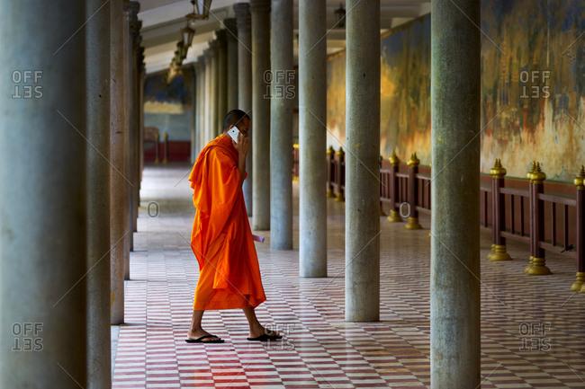 Phnom Penh, Cambodia - December 10, 2016: Monk talking on smart phone - Royal Palace, Phnom Penh