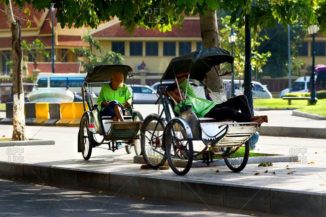 Phnom Penh, Cambodia - December 10, 2016: Cambodian cyclo drivers and their cyclos