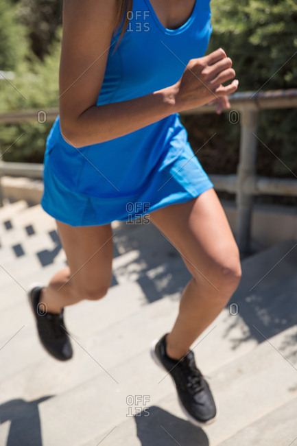 Fit woman working out and running stairs outdoors.
