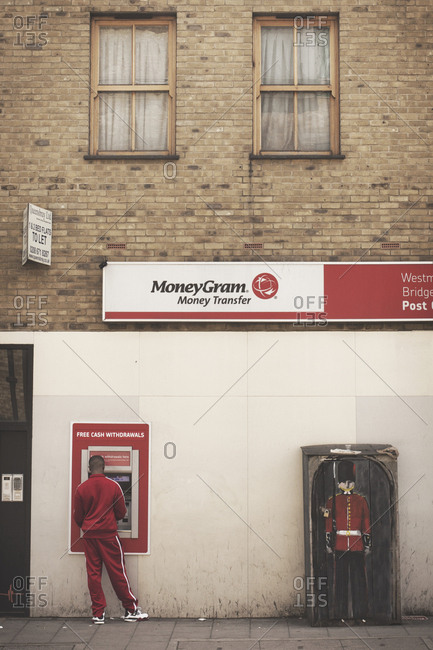London, United Kingdom - May 6, 2013: Man is cashing money at a Money Gram ATM in London