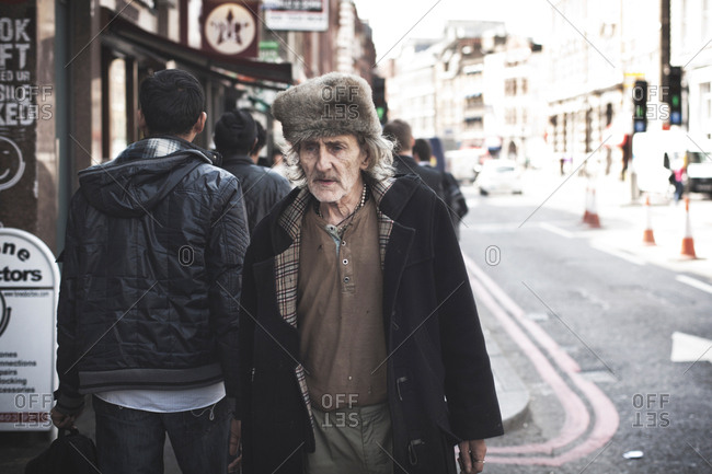London, United Kingdom - May 7, 2013: An old man wears a fur hat and is walking down the street in London