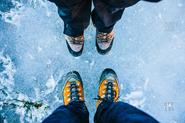 Goldegg, Austria - December 27, 2015: Two pairs of hiking boots on the icy surface of a frozen pond in the mountains near Goldegg
