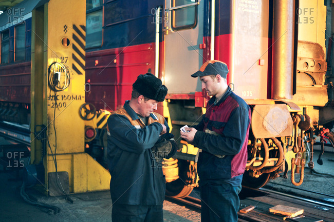 Russian Federation - March 4, 2011: Two train workers are having a break and a cigarette at an unknown train station in Russia
