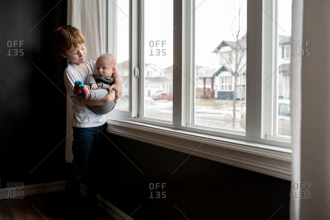 Boy holding his baby brother standing next to window
