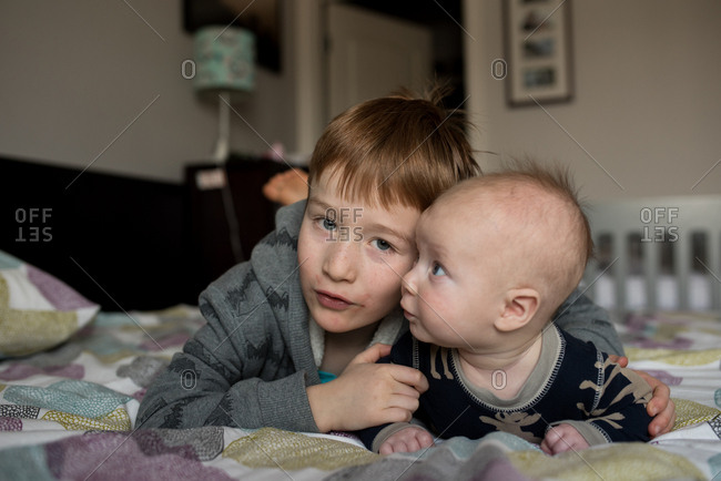 Boy lying on the bed with his baby brother looking up at him