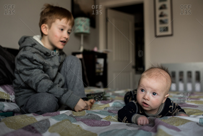 Baby on bed with his older brother sitting next to him