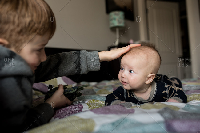 Boy gently touching his baby brother's head
