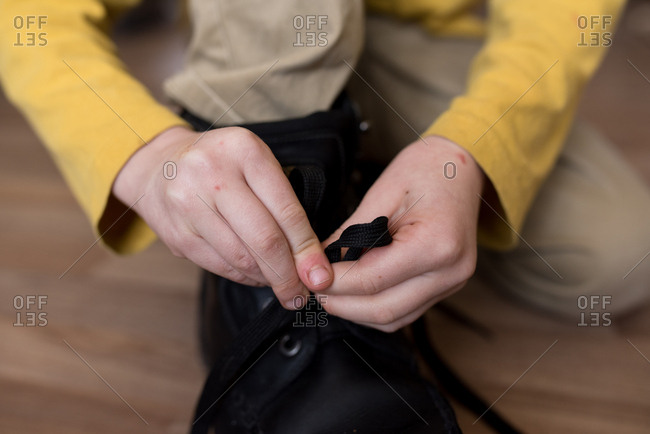 Close-up of a boy tying his shoes