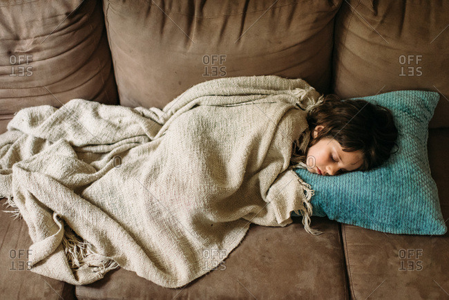Young girl sleeping under a blanket on a couch.