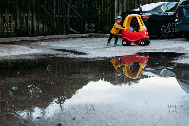 Toddler pushing older sister in a toy car through a big puddle.