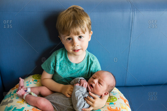 Big brother holding newborn baby for the first time