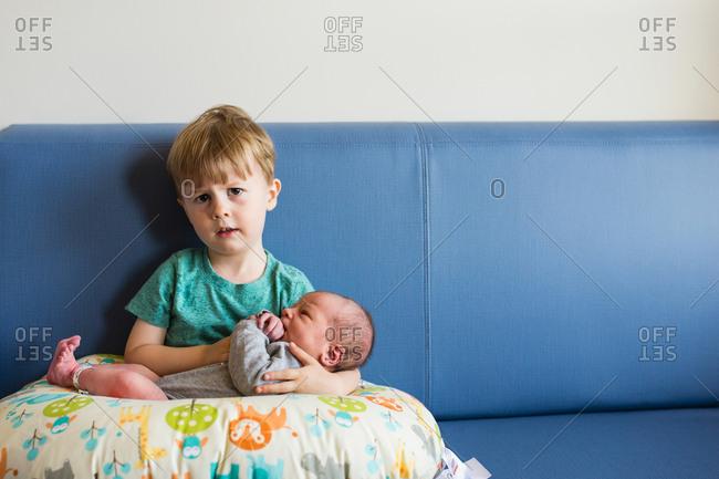 Big brother holding newborn baby on blue sofa