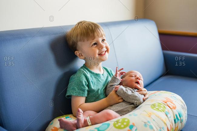 Happy big brother holding newborn baby